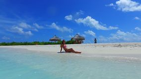 P02735 Maldives white sandy beach 1 person young beautiful woman relaxing on sunny tropical paradise island with aqua Stock Photos