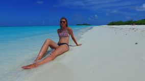 P02734 Maldives white sandy beach 1 person young beautiful woman relaxing on sunny tropical paradise island with aqua Stock Photo