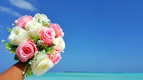 P00702 Maldives white sandy beach pink bouquet flowers on sunny tropical paradise island with aqua blue sky sea ocean 4k. Maldives white sandy beach pink bouquet Royalty Free Stock Photos
