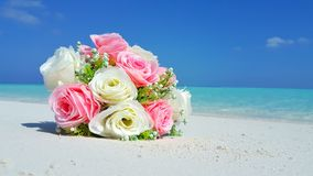 P00709 Maldives white sandy beach pink bouquet flowers on sunny tropical paradise island with aqua blue sky sea ocean 4k Stock Image