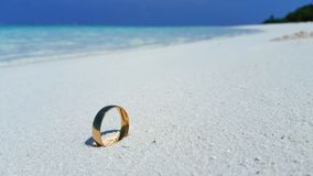 P00782 Maldives white sandy beach wedding engagement gold ring on sunny tropical paradise island with aqua blue sky sea ocean 4k Royalty Free Stock Photos