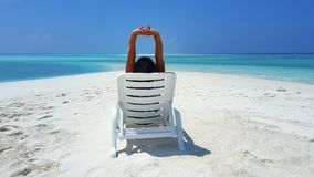 P01746 Maldives white sandy beach young woman relaxing on sunbed on sunny tropical paradise island with aqua blue sky. Maldives white sandy beach young woman Royalty Free Stock Photos