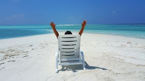 P01748 Maldives white sandy beach young woman relaxing on sunbed on sunny tropical paradise island with aqua blue sky Royalty Free Stock Images