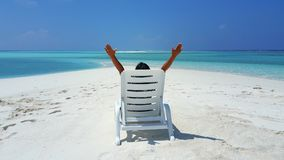 P01749 Maldives white sandy beach young woman relaxing on sunbed on sunny tropical paradise island with aqua blue sky Stock Image