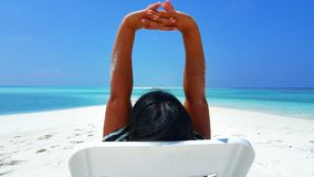 P01752 Maldives white sandy beach young woman relaxing on sunbed on sunny tropical paradise island with aqua blue sky Royalty Free Stock Photography