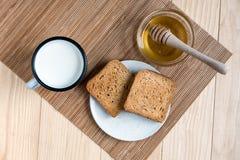 P?o do brinde com Tin Mug do leite e do frasco do mel imagem de stock royalty free