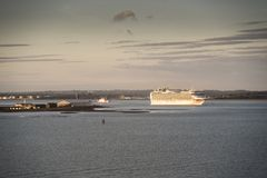 P&O`s Azura in the Solent at sunset. P&O`s Azura in the Solent at sunset. The Azura is just passing the spit from Calshot water sports centre and in the Royalty Free Stock Photo