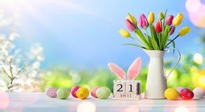 P?ques - date civile avec les oeufs et les tulipes d?cor?s images stock