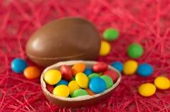 P?ques Les oeufs de chocolat avec les sucreries multicolores se trouvent sur un fond rose photo libre de droits