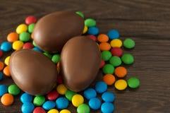 P?ques Les oeufs de chocolat avec les sucreries multicolores se trouvent sur une table brune en bois image libre de droits