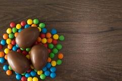 P?ques Les oeufs de chocolat avec les sucreries multicolores se trouvent sur une table brune en bois images stock