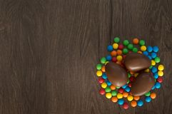 P?ques Les oeufs de chocolat avec les sucreries multicolores se trouvent sur une table brune en bois image stock
