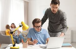 P?re aidant son fils d'adolescent avec le travail image stock