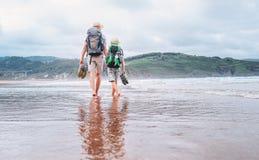 P?re avec la promenade de fils nu-pieds sur la plage d'oc?an de sable images stock