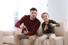 P?re et fils jouant des jeux vid?o image libre de droits