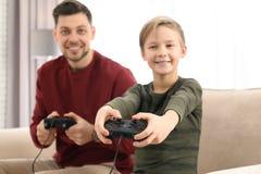 P?re et fils jouant des jeux vid?o photographie stock