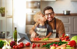 P?re heureux de famille avec le fils pr?parant la salade v?g?tale images stock