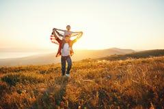 P?re heureux et enfant de famille avec le drapeau des Etats-Unis appr?ciant le coucher du soleil sur la nature images stock