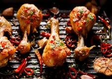 P?s de galinha grelhados picantes, pil?es com a adi??o de pimentas de piment?o, alho e ervas na placa da grade, vista superior foto de stock royalty free
