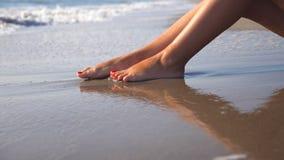 P?s f?meas bonitos que encontram-se na areia e que relaxam perto da costa de mar Jovem mulher que senta-se na costa e que bronzea vídeos de arquivo