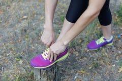 P?s f?meas Mulher nas sapatilhas lilás brilhantes dos laços pretos do sportswear com os laços do cal, preparando-se para um movim imagem de stock
