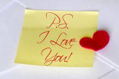 P.S. I Love You!. A  felt heart over a sticky note with P.S. I Love You! text Stock Images