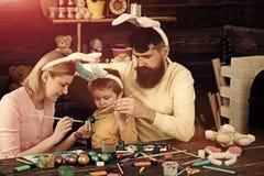 P?scoa Bunny Costume Ovos da p?scoa da pintura da m?e, do pai e da crian?a imagem de stock royalty free