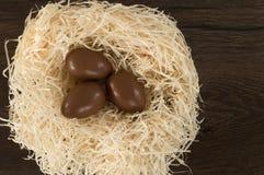 P?scoa Os ovos de chocolate encontram-se em um ninho em uma tabela marrom de madeira fotos de stock