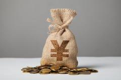 P?se med pengar- och yuankonturn p? gr? bakgrund Symbol av rikedom och h?ga vinster arkivfoto
