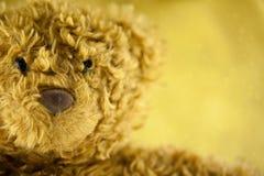 På sydd gullig röd hjärta på en nallebjörn med guld blänka bakgrund, (selektivt fokus) Royaltyfri Fotografi