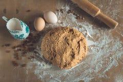 P?te de pain de grenier avec le saupoudrage de la farine et roulement-goupille, oeufs et lait sur la table en bois dans une fin d photo stock