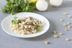 P?tes avec les champignons de paris frits arros?s avec des verts d'un plat blanc sur un fond gris image stock