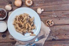 Pâtes italiennes délicieuses de penne avec le champignon de paris crémeux frit de champignons Concept sain Vue supérieure photos stock
