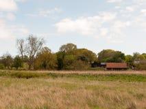País do dia de mola com celeiro, grama e céu fotografia de stock royalty free