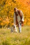 País do outono - cão da caminhada da mulher no prado Imagem de Stock Royalty Free