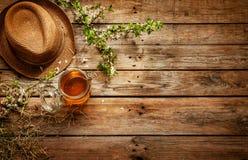 País - tarro de la miel, del sombrero del jardinero y de la rama de árbol floreciente Fotografía de archivo