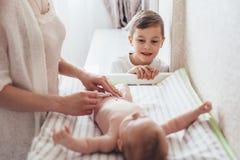 Pañal cambiante de la mamá al bebé imagen de archivo
