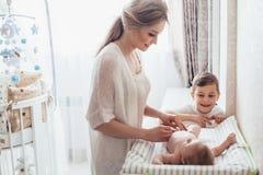 Pañal cambiante de la mamá al bebé fotos de archivo libres de regalías