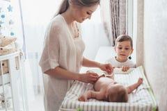Pañal cambiante de la mamá al bebé fotos de archivo