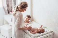 Pañal cambiante de la mamá al bebé imágenes de archivo libres de regalías