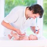 Pañal cambiante del padre cariñoso joven de su hijo recién nacido del bebé Imagenes de archivo