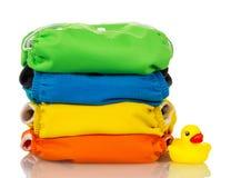 Pañales orgánicos del paño y pato de goma aislados en blanco Imagen de archivo libre de regalías