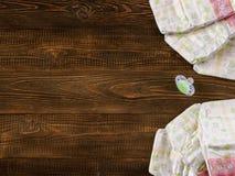 Pañales y maniquí disponibles en fondo de madera Foto de archivo