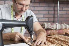 Paño de costura del sastre de sexo masculino maduro en la máquina de coser Imágenes de archivo libres de regalías