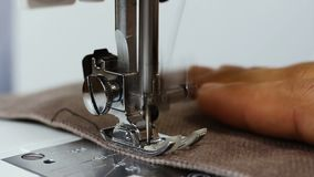 Paño de la tenencia de la mano de la costurera del hombre detrás de la máquina de coser coser la tela almacen de metraje de vídeo
