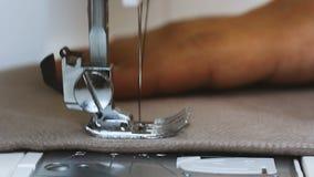 Paño de la tenencia de la mano de la costurera del hombre detrás de la máquina de coser metrajes