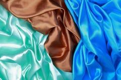 Paño de seda azul y marrón y verde claro del satén del te ondulado de los dobleces Foto de archivo