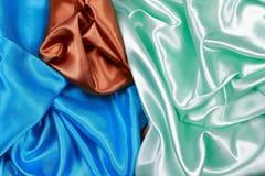 Paño de seda azul y marrón y verde claro del satén del te ondulado de los dobleces fotos de archivo