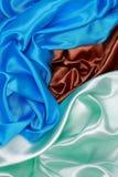 Paño de seda azul y marrón y verde claro del satén del te ondulado de los dobleces fotografía de archivo libre de regalías