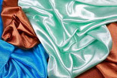Paño de seda azul y marrón y verde claro del satén del te ondulado de los dobleces Imágenes de archivo libres de regalías